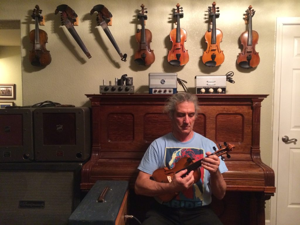 plucking violin in front of violins on the wall